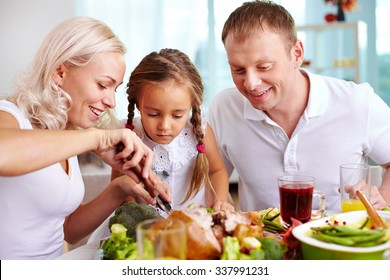 Family of three sitting at the table and going to eat roasted turkey