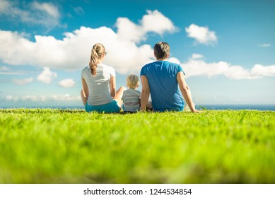 Family of three sitting together in the park.