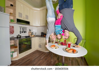 Family of three upside down holds a table in the kitchen with fridge and dishes