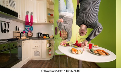 Family of three upside down in the kitchen with table and dishes