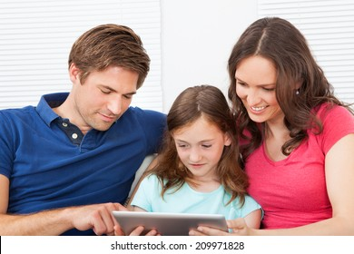 Family of three using digital tablet together while relaxing on sofa at home