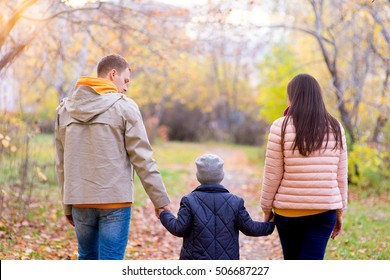 Family of three walks in the autumn park holding hands on the road between the trees