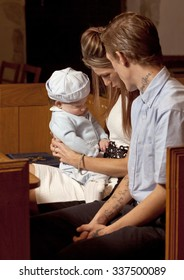 Family of Three.  A young family sit in church after the christening of their young baby boy.