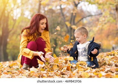 Family throwing leaves in the autumn park