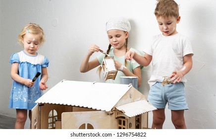 Family time: Children paint a toy house made of plywood for dolls in white.