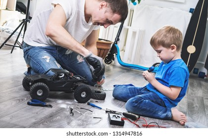 Family time: dad and son little boy repairing a model radio-controlled car at home.