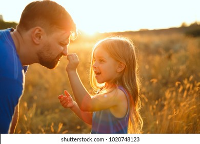 Family time. Father and daughter on the meadow at sunset. A little girl is pinching her father's nose. Back light. Leisure together.