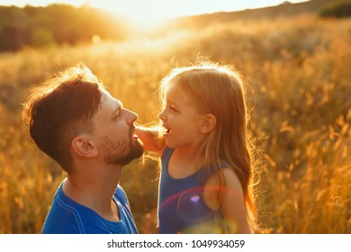 Family time. Father and daughter on the meadow at sunset. A little girl is fluttering her father's hair. Back light. Leisure together.