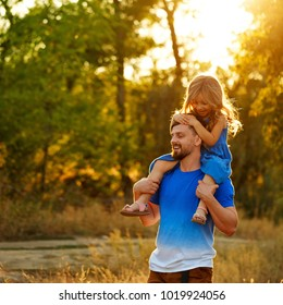 Family time. The father holds the daughter on the shoulders of piggyback. Walk in the park. They laugh and rejoice.