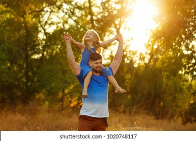 Family time. The father holds the daughter on the shoulders of piggyback. Walk in the park at sunset. They laugh and rejoice.
