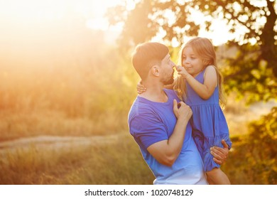 Family time. The father holds the daughter in his arms. The little girl hugs him and touches his nose. They laugh and smile. Leisure together.