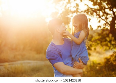 Family time. The father holds the daughter in his arms. A little girl looks into his eyes. Free time together.
