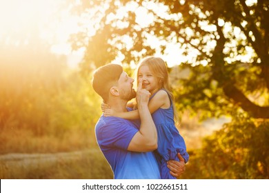 Family time. The father holds the daughter in her arms and touches her nose. The little girl hugs him. They laugh and smile. Leisure together.