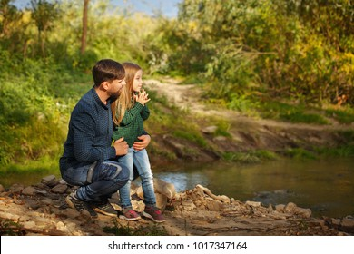 Family time. Father and little daughter are walking by the river. They look at the water. Leisure together.