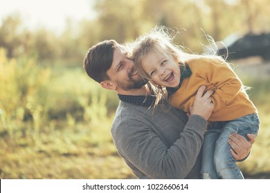 Family time. Father and little daughter together. He tickles her, and she laughs. They are dressed in sweaters. Leisure.