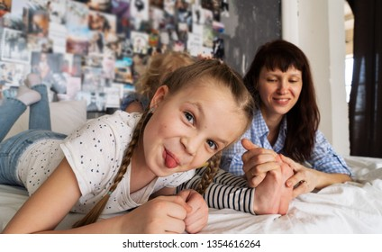 Family time: The girl lies on the bed with her mother, makes faces and shows her tongue.