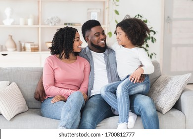 Family Time. Happy African American Parents Bonding With Their Little Daughter At Home, Sitting On Couch In Living Room Together And Smiling