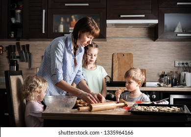Family time: Mom with three children preparing cookies in the kitchen. Real authentic family.