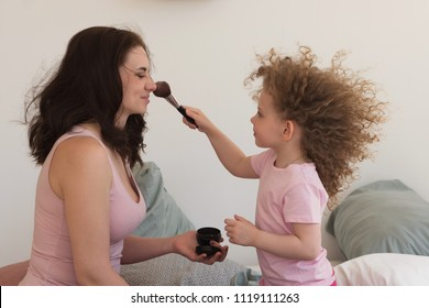 Family time. Mother and daughter together at home. Little girl with curly hair powder brush to apply makeup on her mother's face.