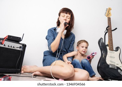 Family time: mother with son staged a home concert and sing with a microphone and an electric guitar.