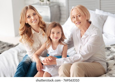 Family time. Positive cheerful delighted sitting on the bed and smiling while enjoying their time together