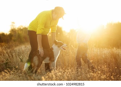 Family time. A pregnant mother walks with her son and dog. Rear sunset light.