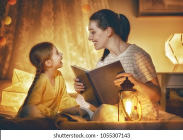 Family time. Pretty young mother reading a book to her daughter. Happy time at home.