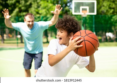 Family Time. Son and dad enjoying basketball game with fun, man running to his kid, trying to steal the ball