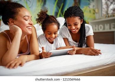 Family time-Smiling cute girl playing with mother and sister at home in a bed on digital tablet