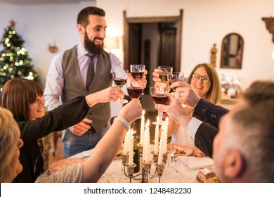 Family toasting and celebrating Christmas and New Year at home. Big group of people at home around the table cheering with wine glasses during holidays