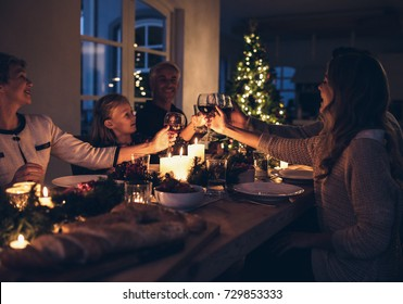 Family toasting with wine in a christmas dinner at home in the living room. Happy family celebrating christmas together at home.
