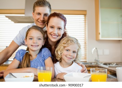 Family together with breakfast behind the kitchen counter