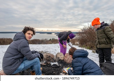 Family together having a winter outdoor picnic and grill. Snow, sky and horizon in the background.
