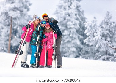 Family together skiing on snowy mountain and looking something in distance