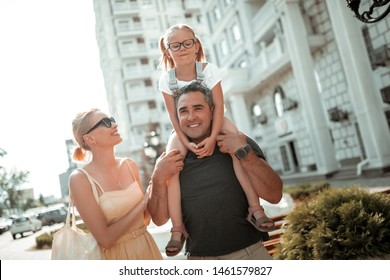 Family together. Smiling little girl sitting on the shoulders of her father walking near her cheerful mother.