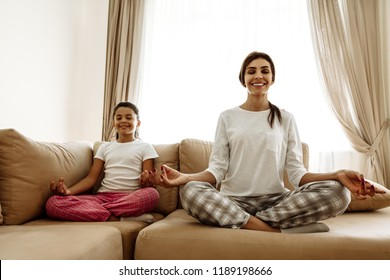 Family. Togetherness. Harmony. Mom and daughter in pajamas are meditating and smiling while sitting in yoga positions on the couch at home