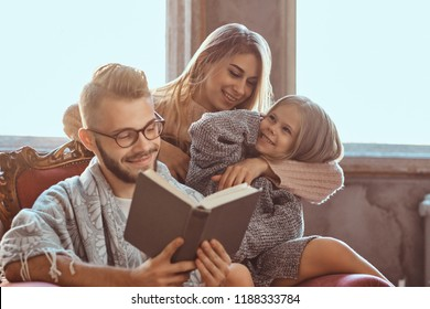 Family togetherness. Mom, dad and daughter reading story book together sitting on the couch. Family and Parenthood Concept.