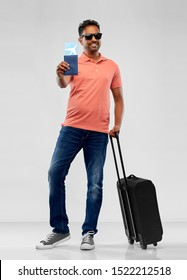 family, tourism and vacation concept - smiling indian man in polo shirt with travel bag, passport and air ticket over grey background