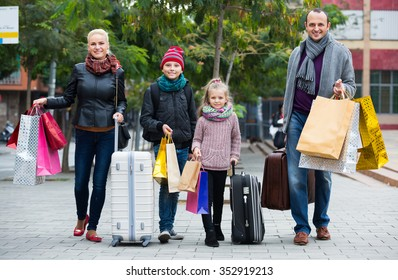 Family of tourists with kids carrying a shopping bags outdoors