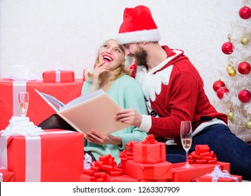 Family tradition. Couple in love enjoy christmas. Happy flashback. Family cuddle near christmas tree while looking family photo album. Remember bright moments of year. Celebrating new year together.