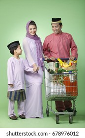 family  with traditional outfit with shopping trolley
