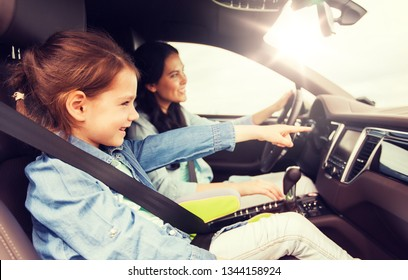 family, transport, road trip and people concept - happy woman with little daughter driving in car
