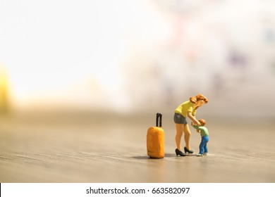 Family and travel concept. Mother and son miniature people figures with orange luggage standing, playing, take care child on wooden ground with map as background.