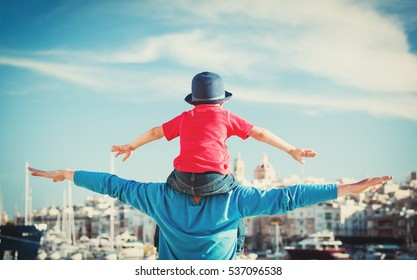 family travel - father and little son on shoulders play at sky