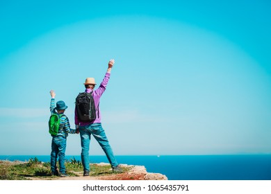 family travel - father and son hiking in mountains at sea