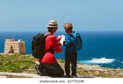 family travel -father and son looking at map in nature