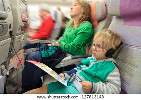 family travel - mother and little boy with headset in flight