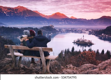 Family travel Slovenia, Europe. Bled Lake one of most amazing tourist attractions. Winter landscape. Top view on Island with Catholic Church in Bled Lake with Castle and Alps Mountains in Background.