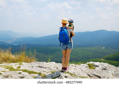 Family travel together in nature park, forest, mountains. Woman and kid boy on vacation. Traveler mother with child on top of high mountain outdoors, looking on beautiful landscape. Rear view.