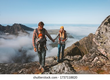 Family travel vacations man and woman hiking with baby carrier outdoor in mountains healthy lifestyle mother and father walking holding hands summer trip in Norway